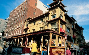 A cable car passes the landmark 1908 Sing Chong Building in Chinatown, San Francisco.