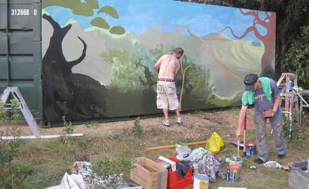 Artists work on the container at Cabarita Beach.