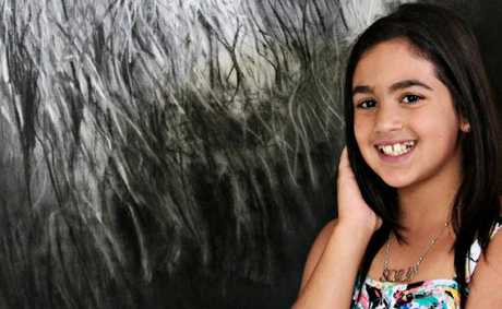 Tia Elsayed, 10, with her charcoal drawing of a lion.