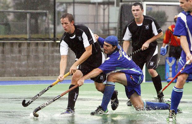 Wests playmaker Todd Watson works hard for possession against a Toowoomba Newtown challenger in Saturday's difficult playing conditions at the Ipswich Hockey Complex.