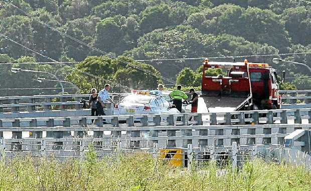 Police officers and a tow truck driver assisting motorists who were hit during a high-speed chase south of Ballina yesterday afternoon.