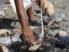 A fisherman cooks lunch on the beach in the Omani port town of Quriyat.