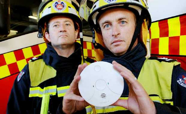 Lismore Fire Brigade senior firefighter Mike Grunske and firefighter Justin Hyde with a photo-electric smoke alarm.