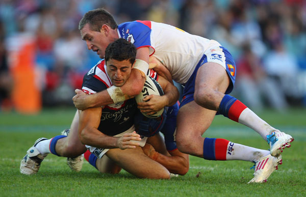 Anthony Minichiello of the Roosters is tackled during the round nine NRL match between the Sydney Roosters and the Newcastle Knights at Allianz Stadium