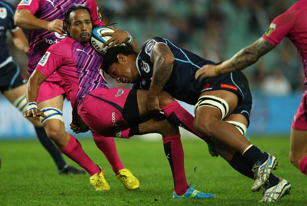 Akona Ndungane of the Bulls is tackled by Lopeti Timani of the Waratahs during the round 12 Super Rugby match between the Waratahs and the Bulls at Allianz Stadium