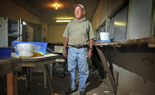 Ulmarra Show and Campdraft Society secretary Alan Watkins looks over dozens of broken plates in the club canteen which was broken into and vandalised.