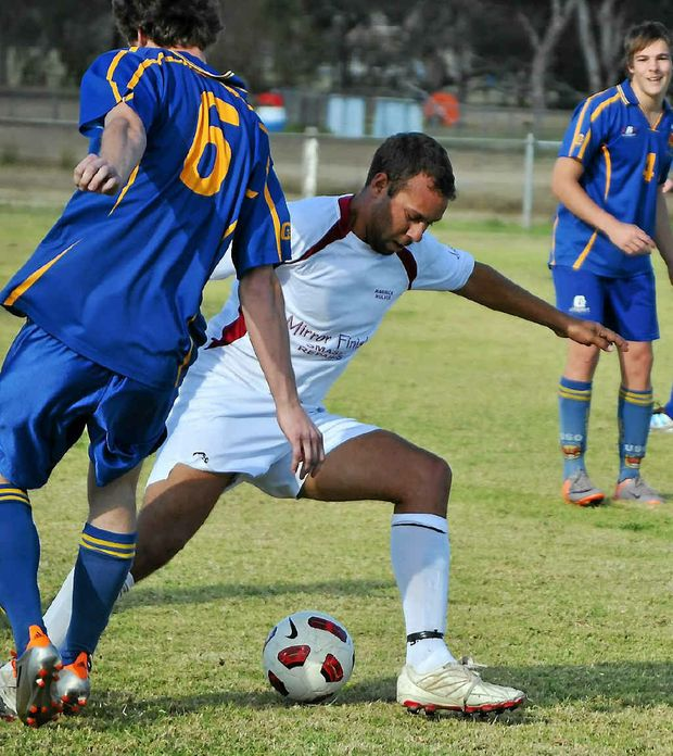 Warwick Wolves player Johnny Enosa (white shirt) tries to beat a USQ opponent.