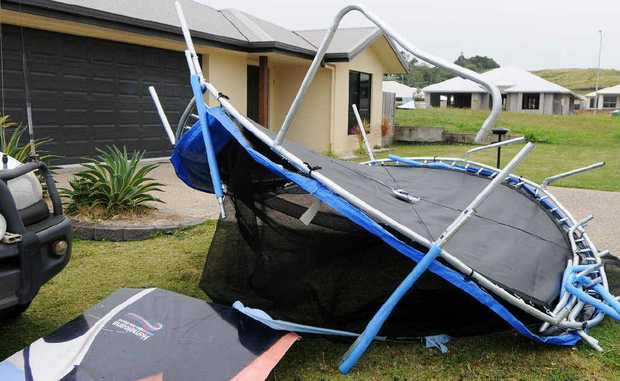 An advertising sign and a trampoline lay damaged on the front yard of a house in Rudd Street, Rural View, after wild winds tore through the area.