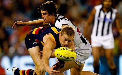 Bernie Vince of Crows tries to handpass while being tackled by Scott Pendlebury of Magpies during the round nine AFL match between the Adelaide Crows and the Collingwood Magpies at AAMI Stadium.