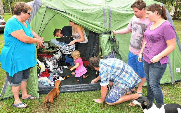 Showing the daily struggle of living in a tent are (from left) Theresa Holtham, Justin Dean, Amanda Holtham, Charlotte Holtham, John Holtham, Richard Holtham and Chenelle Holtham with dogs Sausage and Foxy.