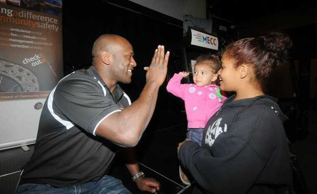 Wendell Sailor high fives Zarlear Ramsamy (small girl) and Lakisha Ramsamy.