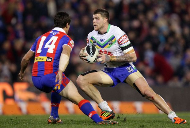 Josh Dugan of the Raiders tries to step around Chris Adams of the Knights during the round 14 NRL match between the Newcastle Knights and the Canberra Raiders at Hunter Stadium