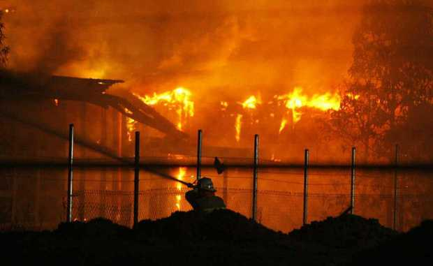 A firefighter hoses the flames which engulfed buildings at the old North Ipswich Railway Workshops.