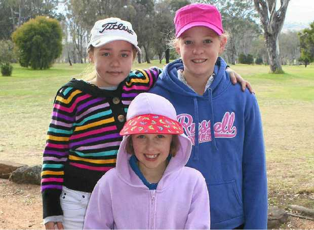 (Back, from left) Lacey Hinze, Eliza McLennan and (front) Samantha Joyce rug up for junior golf.