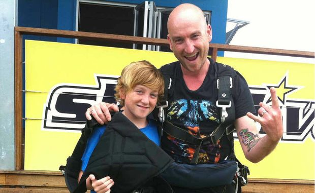 Finn Crofts, 12, with his dad Mick after a skydive.
