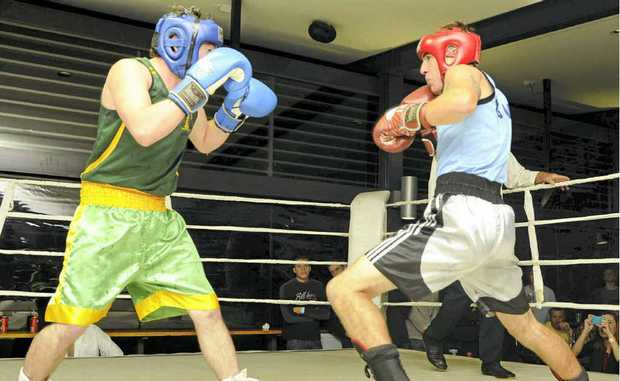 Yamba boxer Keaton Rheinberger (blue singlet) took the North Coast 71kg title against Dorrigo boxer Daniel Glanville (green) at the Yamba Shores Tavern on Saturday night.