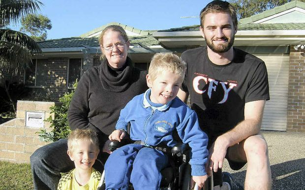 Bailey Jensen (with mum Trish Verran and brother Cooper) in his wheelchair bought thanks to Dane Mitchell (right).