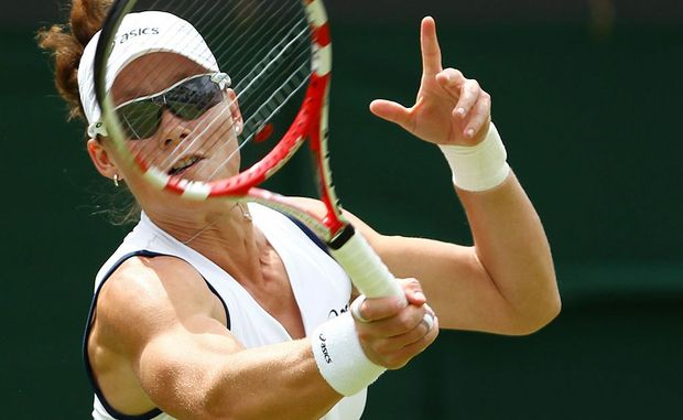 Samantha Stosur of Australia hits a forehand return during her women's singles first round match against Carla Suarez Navarro of Spain on day one of the Wimbledon Lawn Tennis Championships at the All England Lawn Tennis and Croquet Club on June 25, 2012 in London, England.