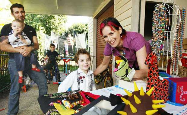 Mother-of-six Bec Draper shows off her fair trade handicrafts to Ezra (front), 3, and husband Brendan with Isaac, 1, and Noah, 9. Mrs Draper has been nominated for The AusMumpreneur Awards.