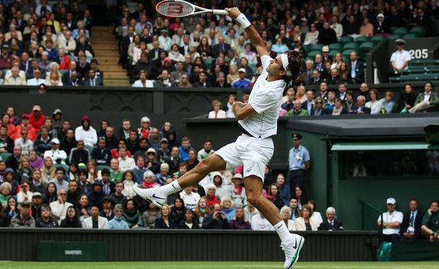 Roger Federer returns the ball during his Gentlemen's Singles fourth round match against Xavier Malisse on day seven of the Wimbledon Lawn Tennis Championships.