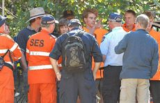 The four relieved young men explain to police and SES volunteers at Finch Hatton Gorge car park how they became lost overnight.
