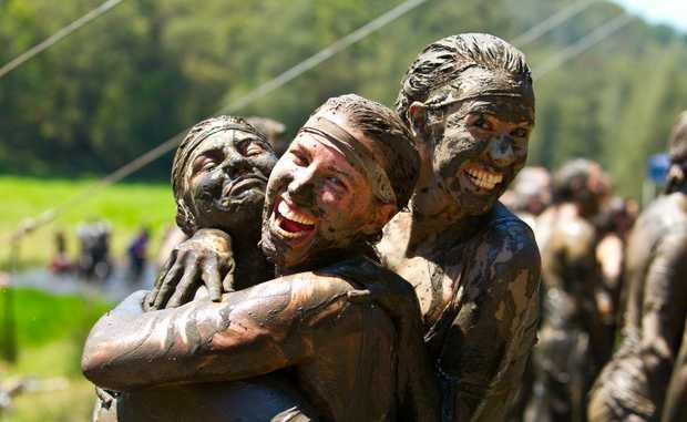 Mud-soaked friends play up the lighter side if the event.