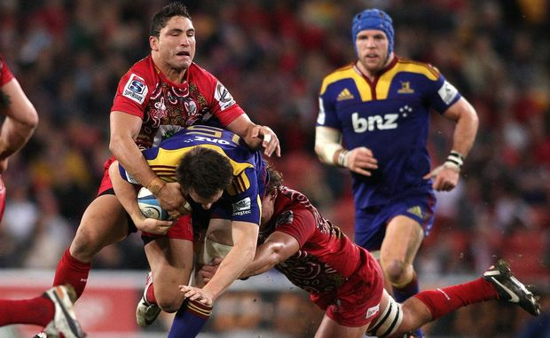 Ben Smith of the Highlanders is tackled by Anthony Faingaa of the Reds during the round 17 Super Rugby match between the Reds and the Highlanders