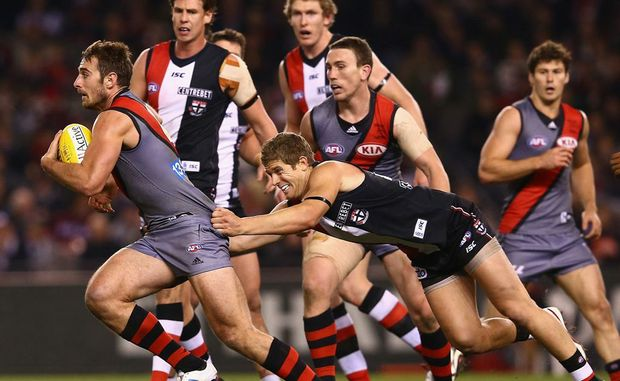 Jobe Watson of the Bombers is tackled by Nick Dal Santo of the Saints during the round 15 AFL match between the St Kilda Saints and the Essendon Bombers at Etihad Stadium