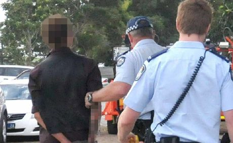 Police officers lead a young man, in handcuffs, from Ooralea Racecourse after an altercation during the Mackay Cup raceday on Saturday.