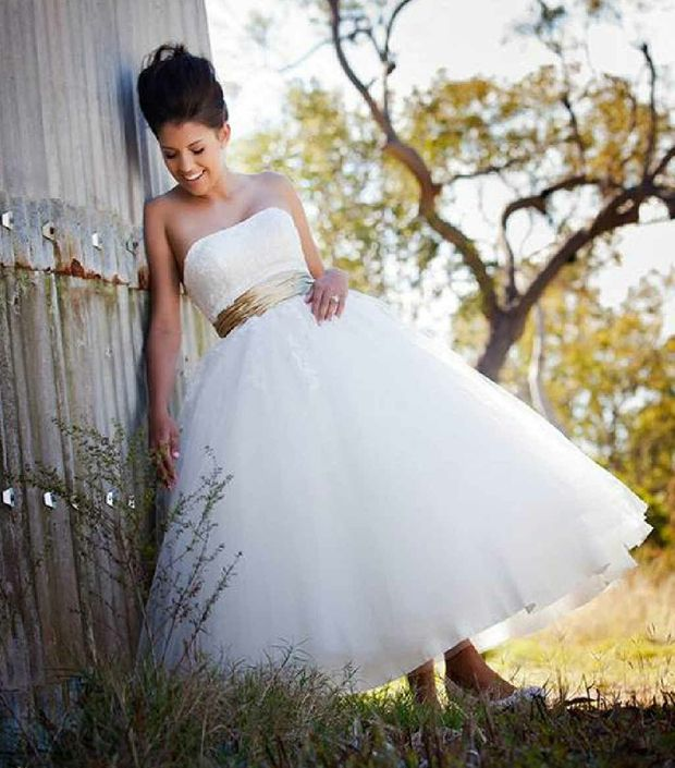 Kelsey Smallwood models a full-skirted gown with a lace bodice and sash.