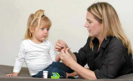 Mum Zoey Synnott checks daughter Alyssa's sugar levels. Alyssa was diagnosed with diabetes when she was 17 months old.