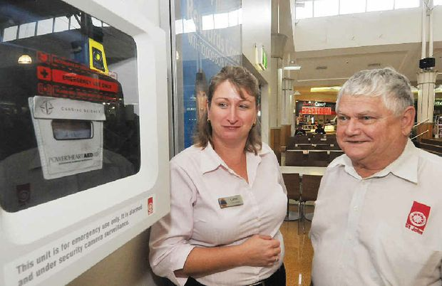 Mount Pleasant Shopping Centre manager Cathy Sullivan and St John Ambulance first aid trainer Graham Lomax near a defibrillator that is mounted on the wall in the food court.