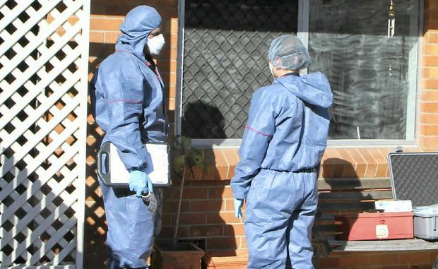Forensic investigators inspect Mr Pullen's Valley St unit.