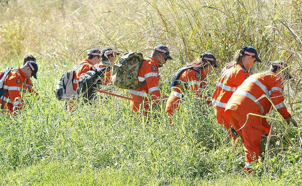 SES volunteers search through grassland at Mt Pleasant for evidence during a police operation in Mackay investigating the disappearance of Timothy Pullen.