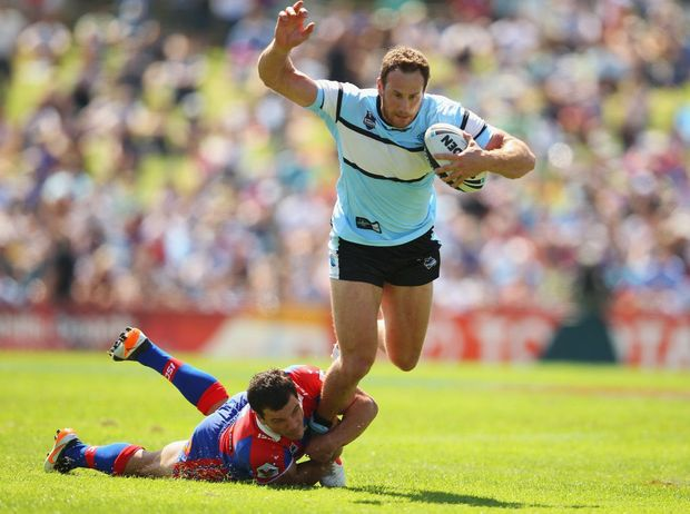 Colin Best of the Sharks is tackled by Jarrod Mullen of the Knights during the round two NRL match between the Cronulla Sharks and the Newcastle Knights at Toyota Stadium on March 11, 2012 in Sydney, Australia.