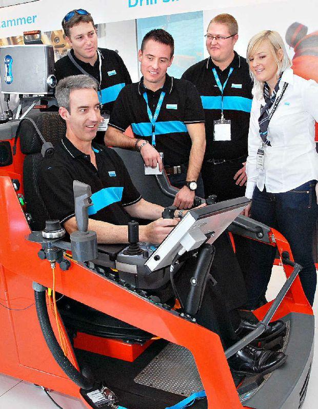 Sandvik staff (from left) Jason Cross, Craig Elgar, Michael Zirbel, Andrew Atkinson and Kate Bills try out the Sim Driller, a simulator-based training system.