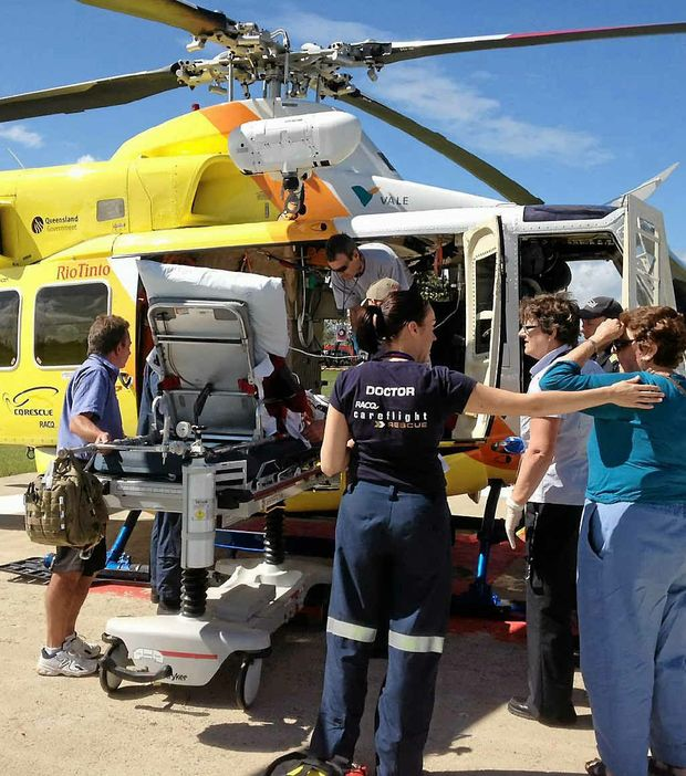 A 73-year-old patient is loaded into the RACQ-CQ Rescue helicopter outside Proserpine Hospital.
