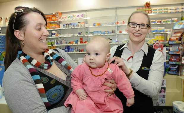 Five-month-old Sarah Hunt tries on an amber teething necklace as mum Jodie Hunt (left) and Judy Wielandt from Southtown Pharmacy look on.