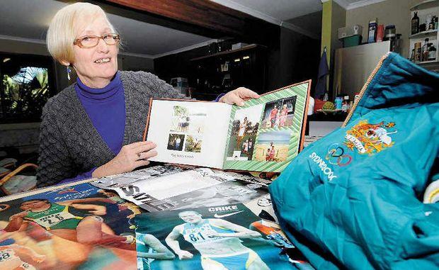 Merilyn Willis, the mother of marathon runner Benita Willis, holds memorabilia of her daughter's long-distance running career.