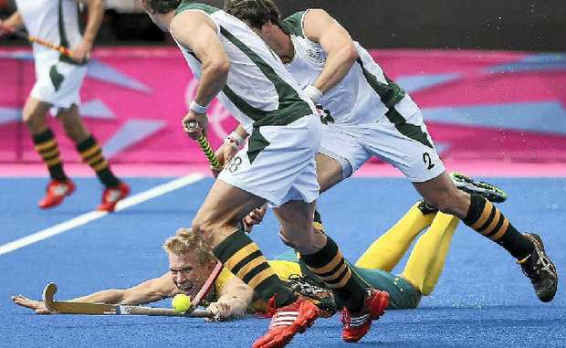Matthew Butturini of Australia fights for the ball against Thorton McDade and Wade Paton of South Africa during the Men's Hockey on Day 3 of the London Olympics.