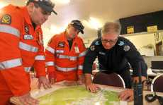 SES Mackay's Brenton Harris, SES Sarina's Sam Roempke and search co-ordinator Mackay police Sergeant Marcus Brown look over maps of the area where police and SES are looking for Sean Russell.