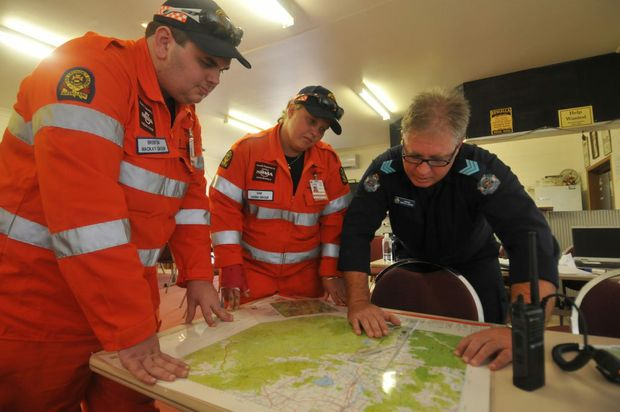 SES Mackay's Brenton Harris, SES Sarina's Sam Roempke and search co-ordinator Sergeant Marcus Brown look over maps of the area where police and SES searched for Sean Russell.