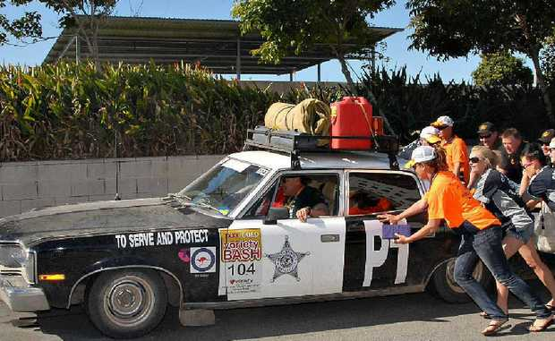 Mackay driver Mark Hunter and co-pilot Michael Bynon, of the Sunshine Coast, get a push after running into mechanical trouble just short of the Variety Bash finish line at Bluewater Quay at the weekend.