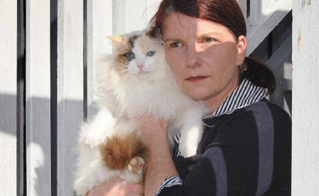 Julie Marshall keeps her cat 'Teacup' close after the shock of finding her other pet cat 'Pyjamas' shot and dying in her front yard on Sunday.