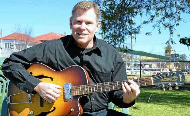 Andrew Carines holds his late uncle's guitar at the Vietnam Veterans Day service at the weekend.
