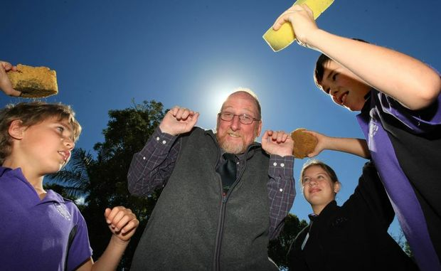 Tyalgum students Jaidyn Larrescy, Rosie Mills and Mitchell Cairns warm up for the sponge throwing contest with principal Peter Meadows.