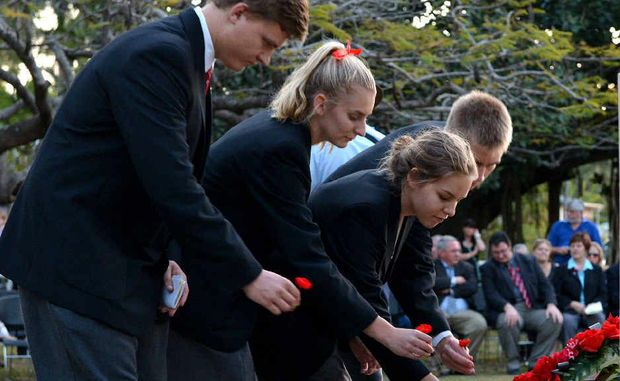 Whitsunday Anglican school students Jimmy van den Heever, Emily Fleming, Sylvie Giguere and Lewis Schmidtke lay poppies in honour of the Rats of Tobruk at Queens Park.