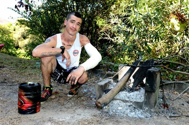 Jesse Lewis with the fuel can and barbecue at his home where he suffered burns.