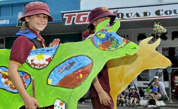 ABOVE: Jessica Ciesiolka from Cambooya State School shows off her colourful cow creation at last weekend's Carnival of Flowers Grand Central Floral Parade in Toowoomba.