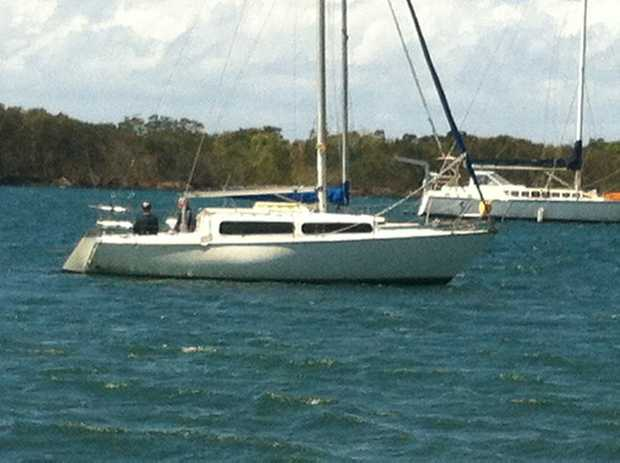 A man was waiting aboard a yacht for rescue after his tinnie capsized in Tweed River and a fellow boatie picked him up.